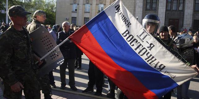 Milicianos prorrusos muestran una bandera rusa frente al edificio regional del Ministerio de Interior, en Lugansk.