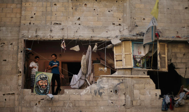 Palestinos, con un cuadro de Arafat, en su casa destruida por los bombardeos.