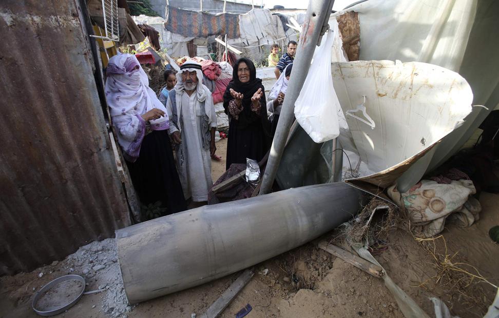 Una mujer palestina observa los restos de una misil que según testigos fue arrojado por la aviación israelí, en una choza de Rafah, en el sur de la Franja de Gaza, este domingo.