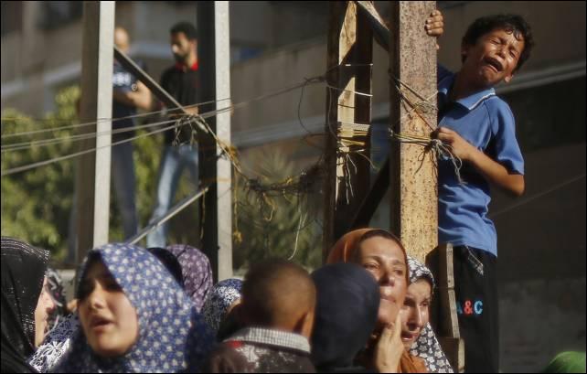 Familiares de los cuatro niños palestinos de la familia Baker, muertos en el bombardeo israelí en la playa de Gaza, lloran durante su funeral.