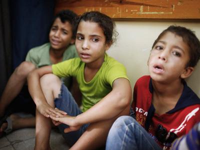 Tres niños palestinos, conmocionados tras sobrevivir a un bombardeo israelí. REUTERS/Finbarr O'Reilly