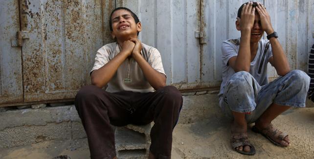 Dos niños lloran junto a los escombros de su casa tras un ataque aéreo de Israel al este de la ciudad de Khanyounis, al sur de la Franja de Gaza.