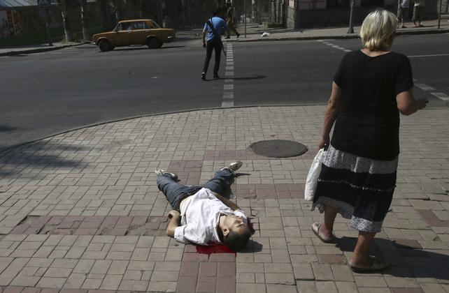 Una mujer permanece junto al cuerpo sin vida de un hombre tras un ataque del ejército ucraniano en el centro de Donetsk.
