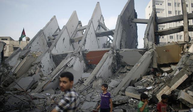 Varios palestinos pasan junto a un edificio destruido durante una bombardeo israelí en la Franja de Gaza.