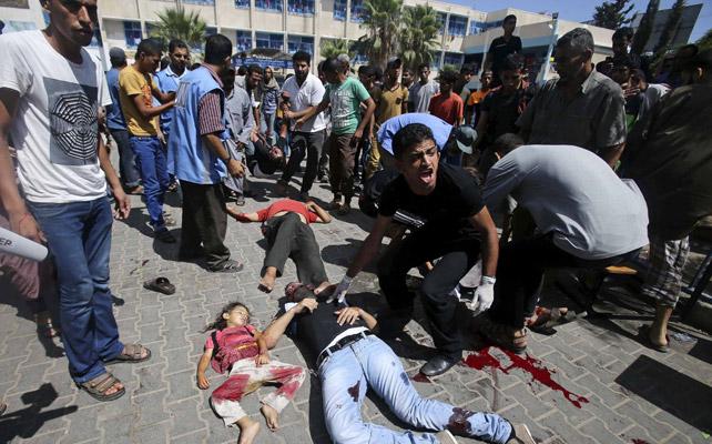 Varios palestinos lloran la muerte de los alcanzados por un misil israelí que atacó este domingo una escuela de la ONU en el sur de Gaza. REUTERS/Ibraheem Abu Mustafa