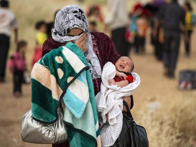 Una joven cruza la frontera de Siria con su hijo en brazos de apenas un mes. ACNUR