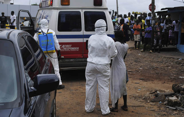 Un sanitario con una mujer sospechosa de estar infectada en Liberia.